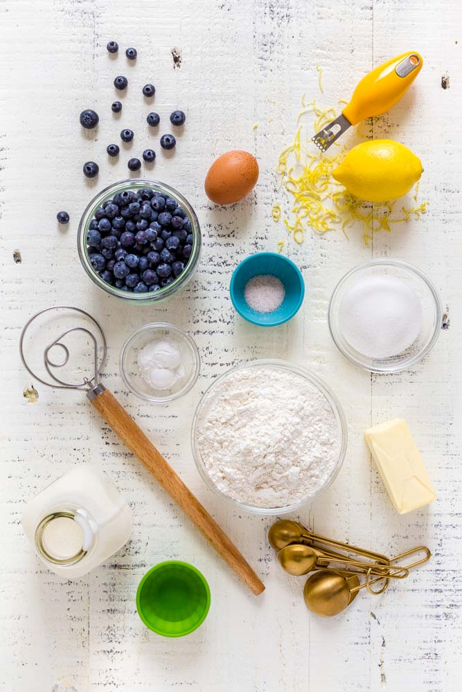 Ingredients for making blueberry scones, along with gold measuring spoons and a dough whisk.