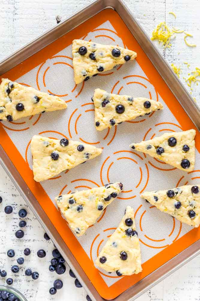 Eight unbaked lemon blueberry scones on a baking tray lined with an orange silicone baking mat.