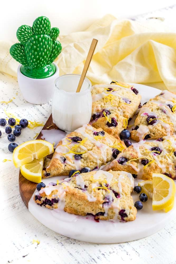 Five lemon blueberry scones on a marble board with a small jar of vanilla glaze.