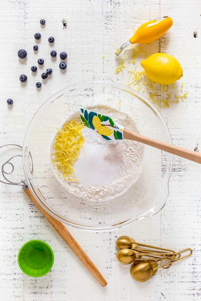 Flour, sugar, baking powder, salt and lemon zest in a clear glass mixing bowl with spatula.