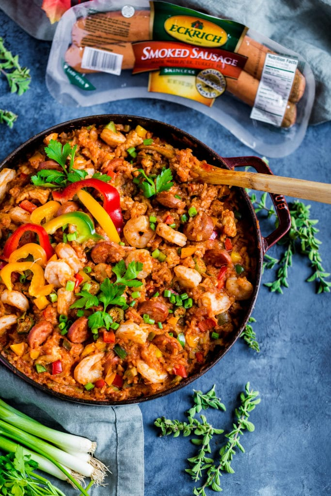 Jambala with sausage, shrimp and chicken served in a cast-iron pan with a wooden spoon.