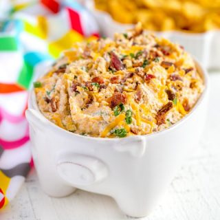 Cheesy Bacon Ranch Dip served in a cute bowl with a side of corn chips.