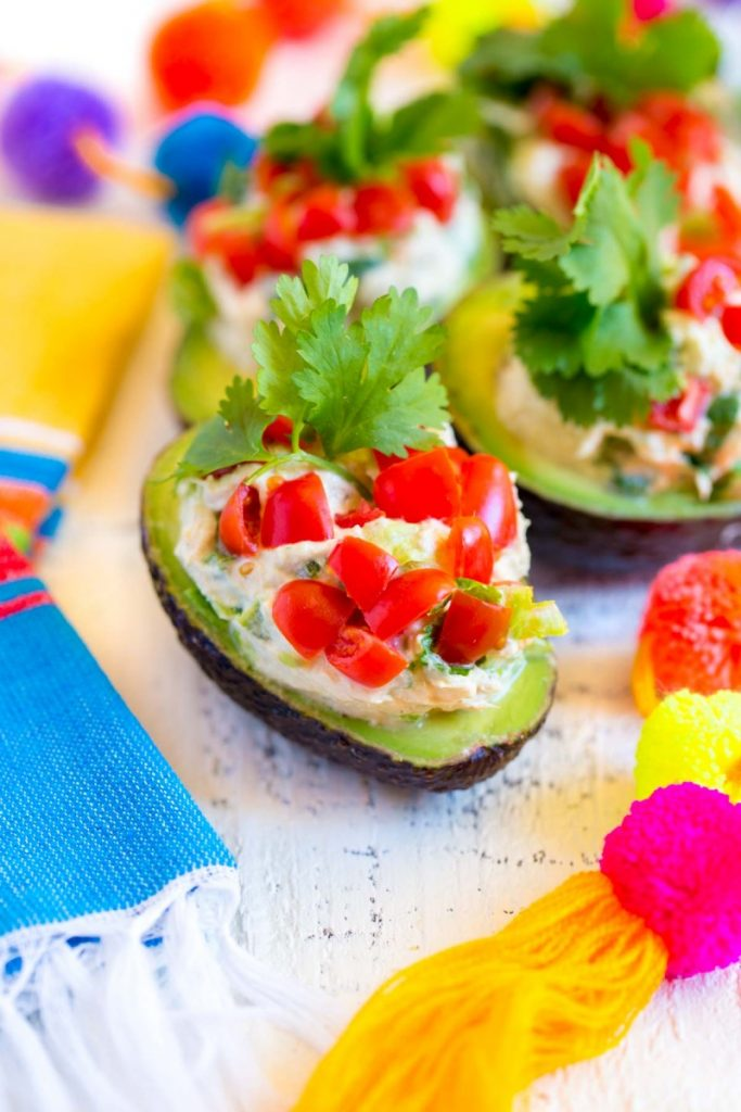 Healthy tuna salad recipe served in avocado halves and garnished with diced tomatoes and a sprig of cilantro.