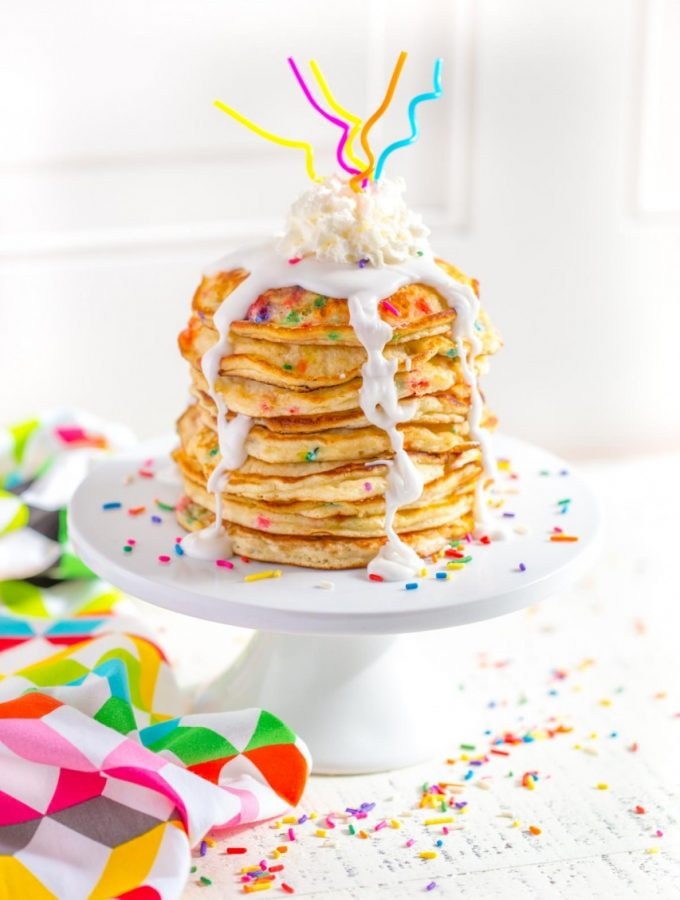 Funfetti Pancakes served on a white cake stand.