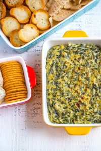 Best Spinach Artichoke Dip served with crackers and chips.
