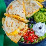 Tex-Mex Cheese Quesadillas served with sides of pico de gallo, sour cream, guacamole and black olives.