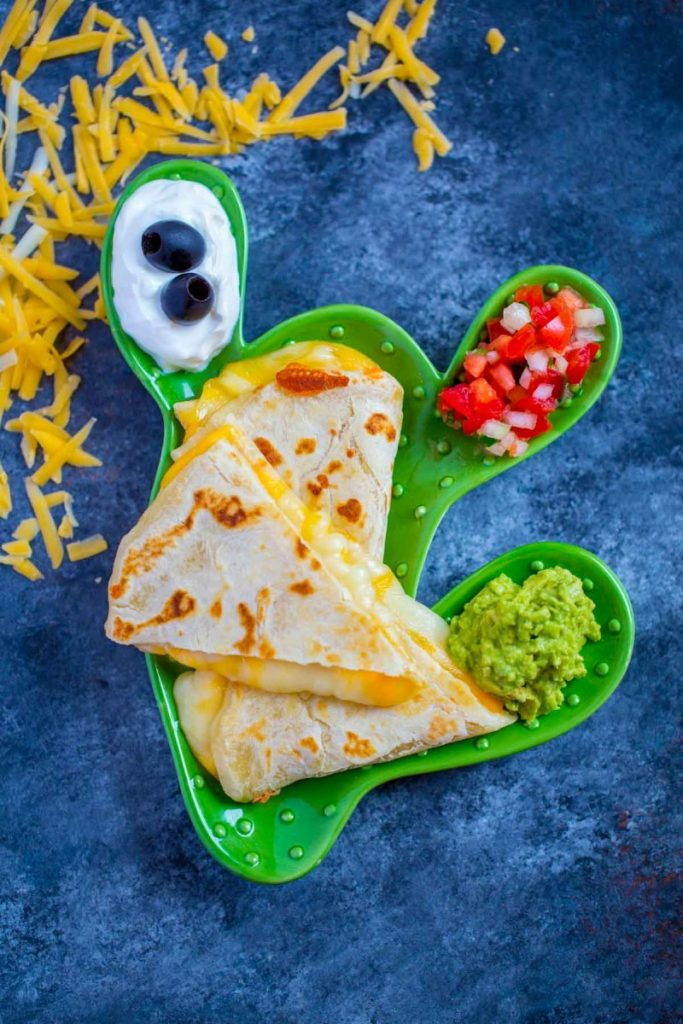 Quesadillas with melted cheese and colorful garnishes.