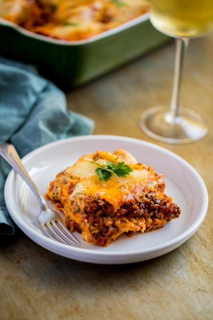 Meat lasagna with ricotta cheese filling, garnished with fresh parsley.