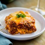 Legendary Meat Lasagna Recipe served with a glass of wine.
