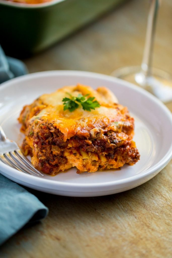 Legendary Meat Lasagna served with a glass of wine.