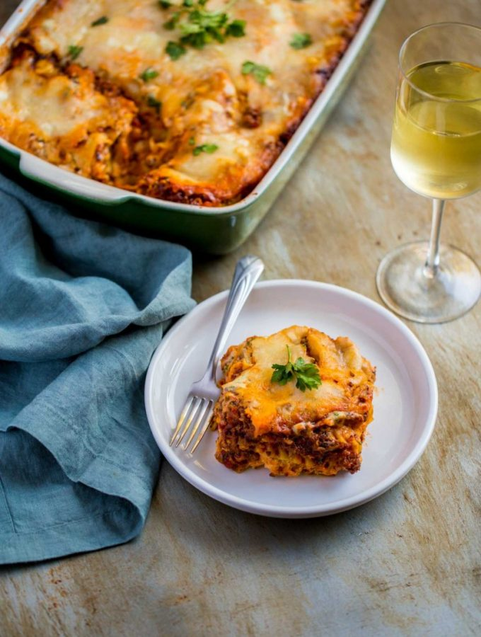 Legendary Homemade Meat Lasagna Recipe made with Ricotta cheese and served with a glass of wine.
