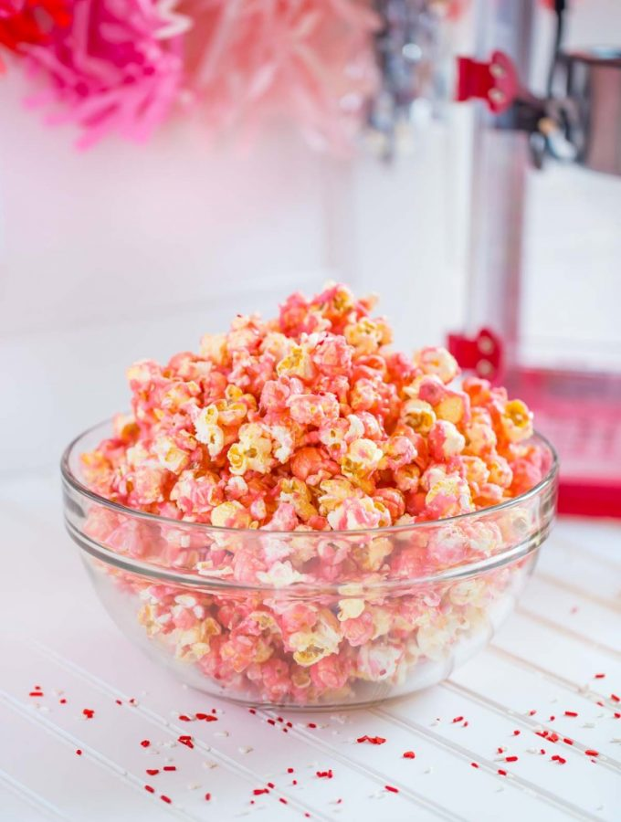 Pink Popcorn served in a clear glass bowl.