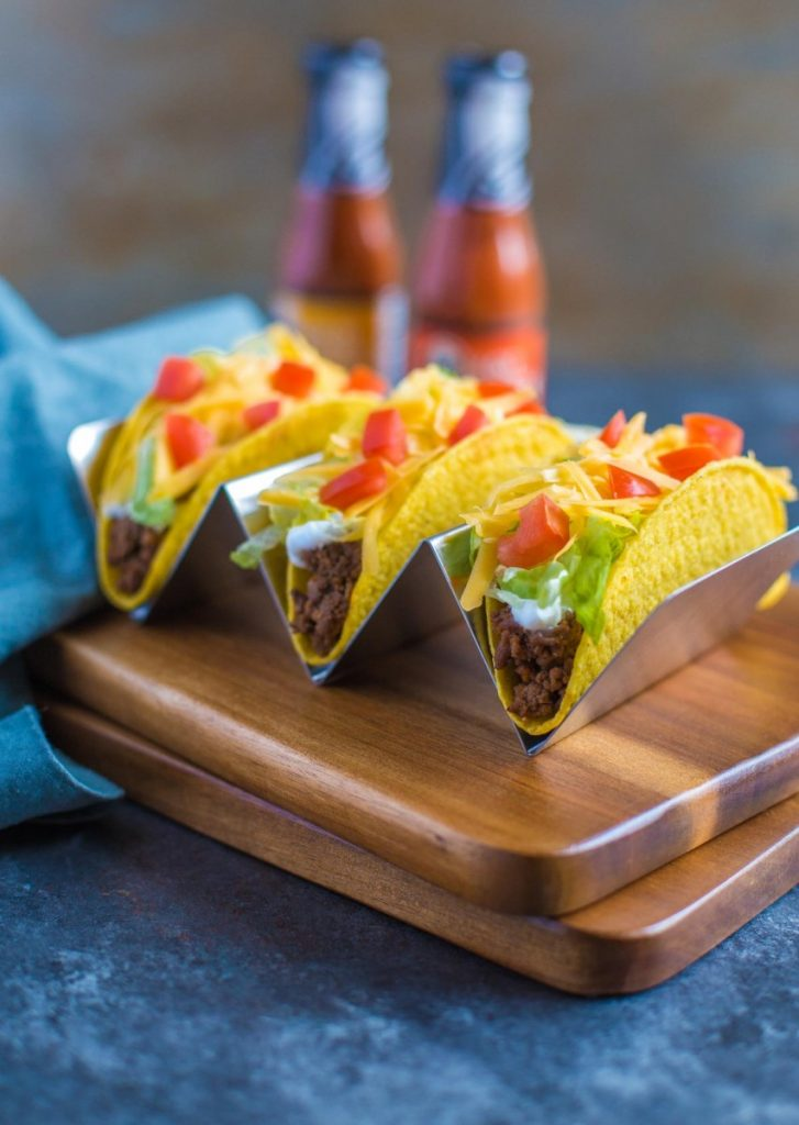 Ground Beef Tacos displayed in a special taco holder along with Taco Bell hot sauce.