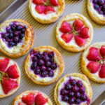 Colorful cream cheese breakfast pastries made with cream cheese, blueberries and strawberries garnished with zest of lime.