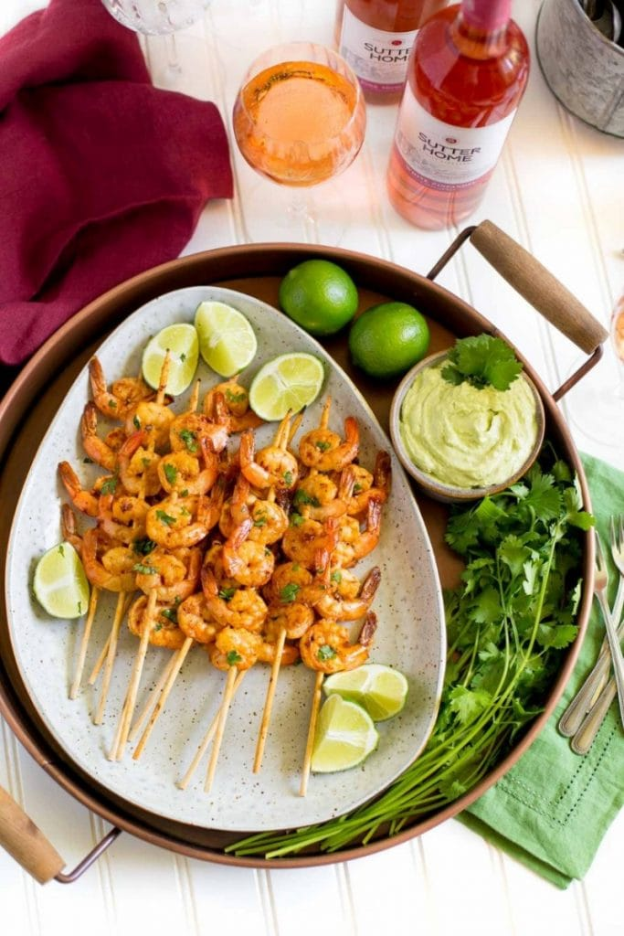 Grilled shrimp on a platter with lime wedges and avocado dipping sauce.