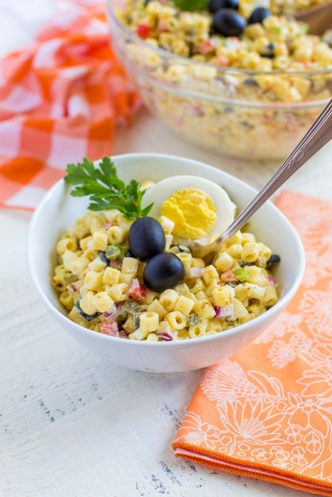 Macaroni salad garnished with egg, olives and parsley