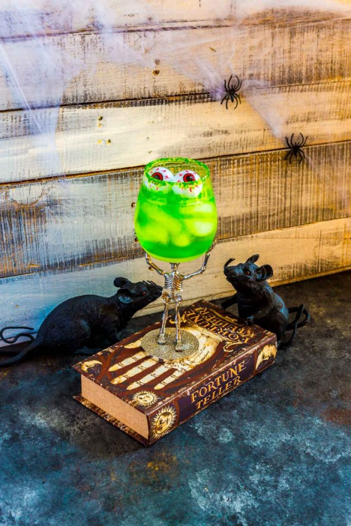 A Halloween tequila cocktail that glows green with Jello served in a scary skeleton glass.