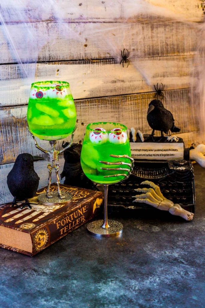 Two swampy green drinks that glow served in Halloween goblets with floating gummy eyeballs.