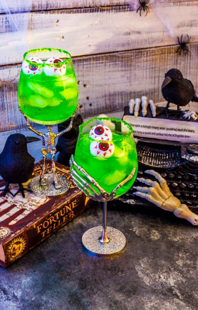 Two adult Halloween beverages next to Halloween table decorations in a spooky setting.