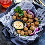 Chicken meatballs in a black serving bowl.