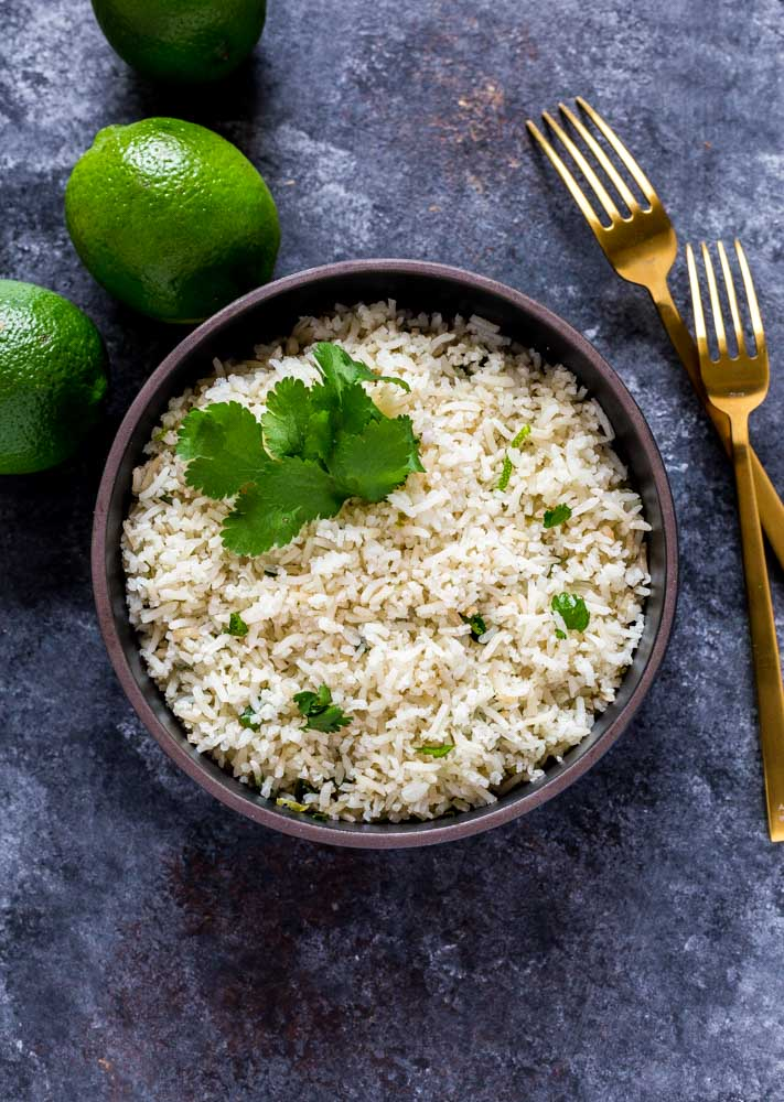 An individual serving of cilantro lime rice garnished with fresh sprigs of cilantro and limes.