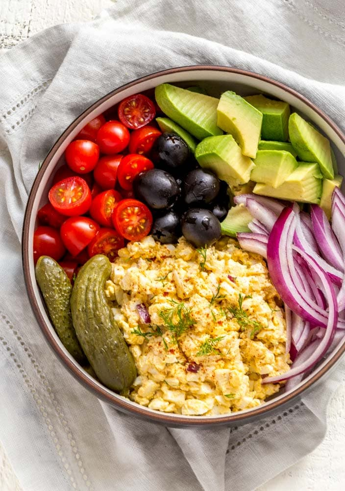 Egg salad with dill in a bowl with cherry tomatoes, pickles, olives, avocado and red onion.