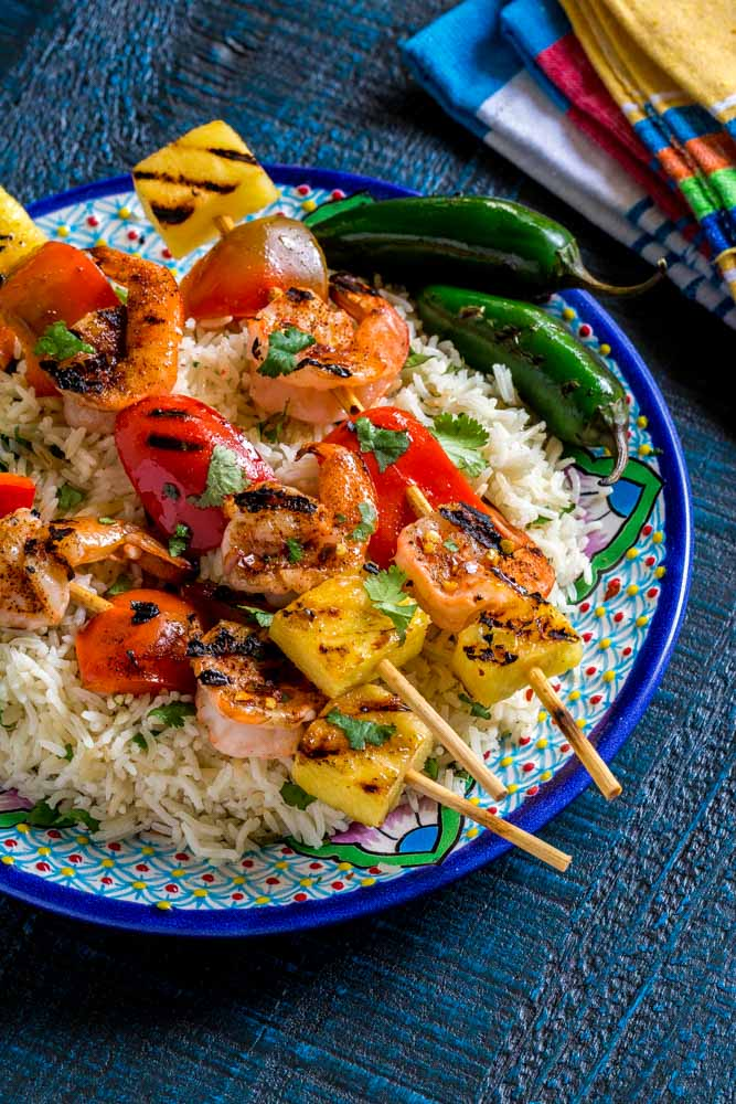 Grilled shrimp skewers on a plate with cilantro lime rice.