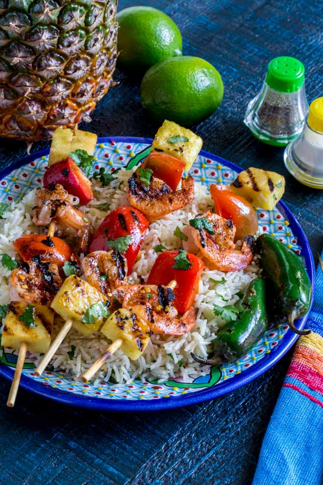 Three shrimp skewers plated over cilantro lime rice with jalapenos on the side.