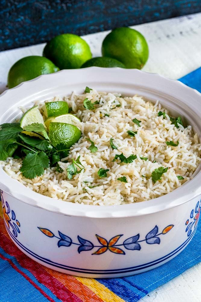 Cilanto Lime Rice in a serving bowl garnished with lime slices and fresh cilantro.