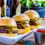 Three cheeseburger sliders on a thin rectangular platter with a pickle and bamboo pick.