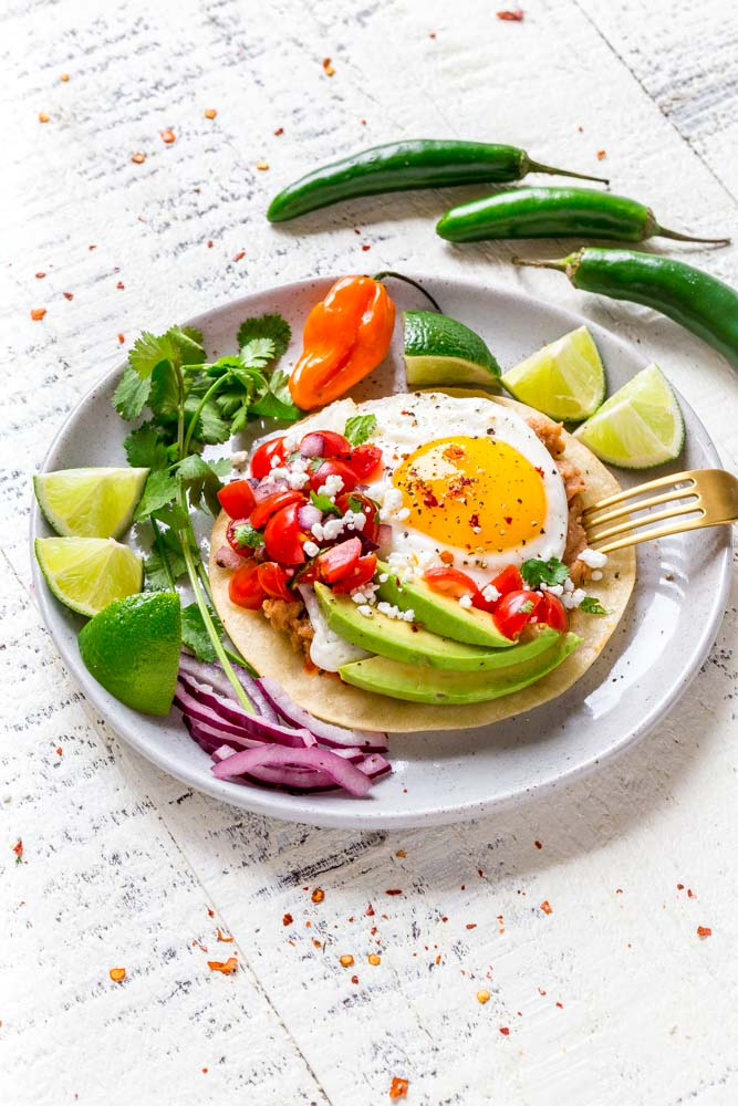 HUEVOS RANCHEROS served with fresh Mexican peppers and slices of lime.