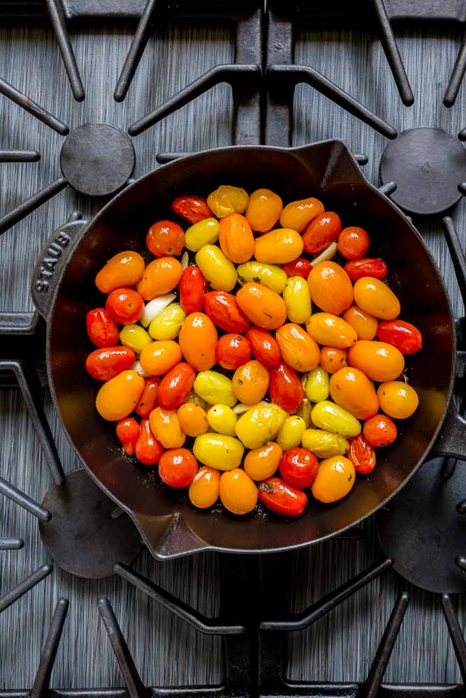 A colorful medley of roasted tomatoes and herbs in a cast-iron skillet on the stovetop.