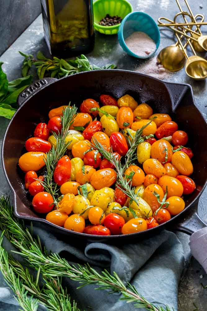 Medley of colorful roasted tomatoes in a cast-iron pan, garnished with sprigs of fresh rosemary.