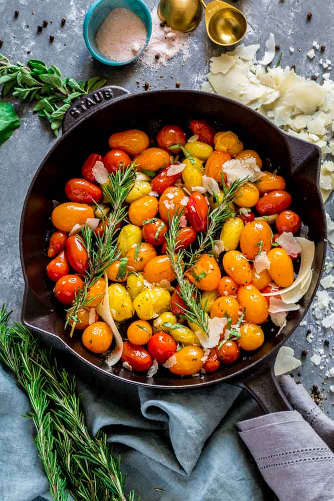 Heirloom cherry tomatoes in a cast iron skillet garnished with herbs and cheese.