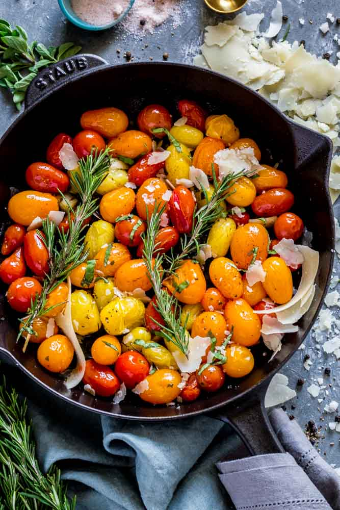 Orange, red and yellow roasted tomatoes garnished with cheese and herbs in a cast-iron skillet.