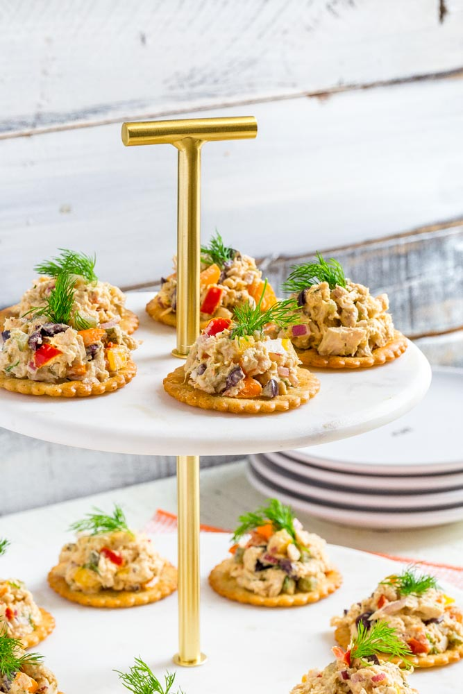 Tuna salad on individual crackers garnished with fresh dill served on a tiered tray.