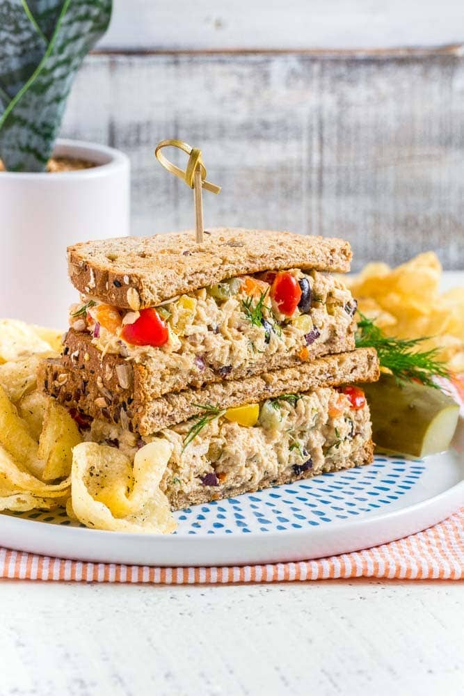 Tuna Salad Sandwich served on a round plate with chips and a pickle.