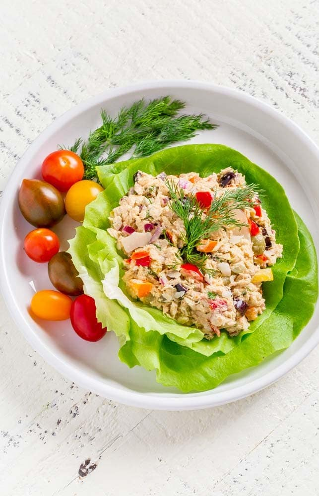 A tuna salad lettuce wrap on a round plate with cherry tomatoes and dill.