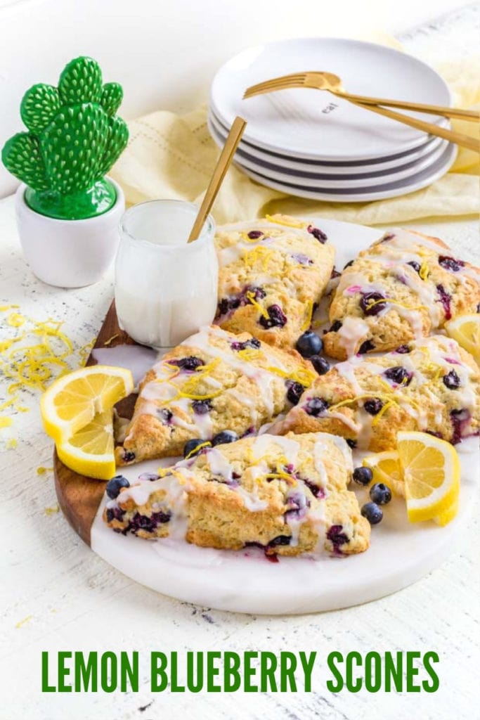 Five blueberry scones with vanilla glaze on a marble board with lemon slices.