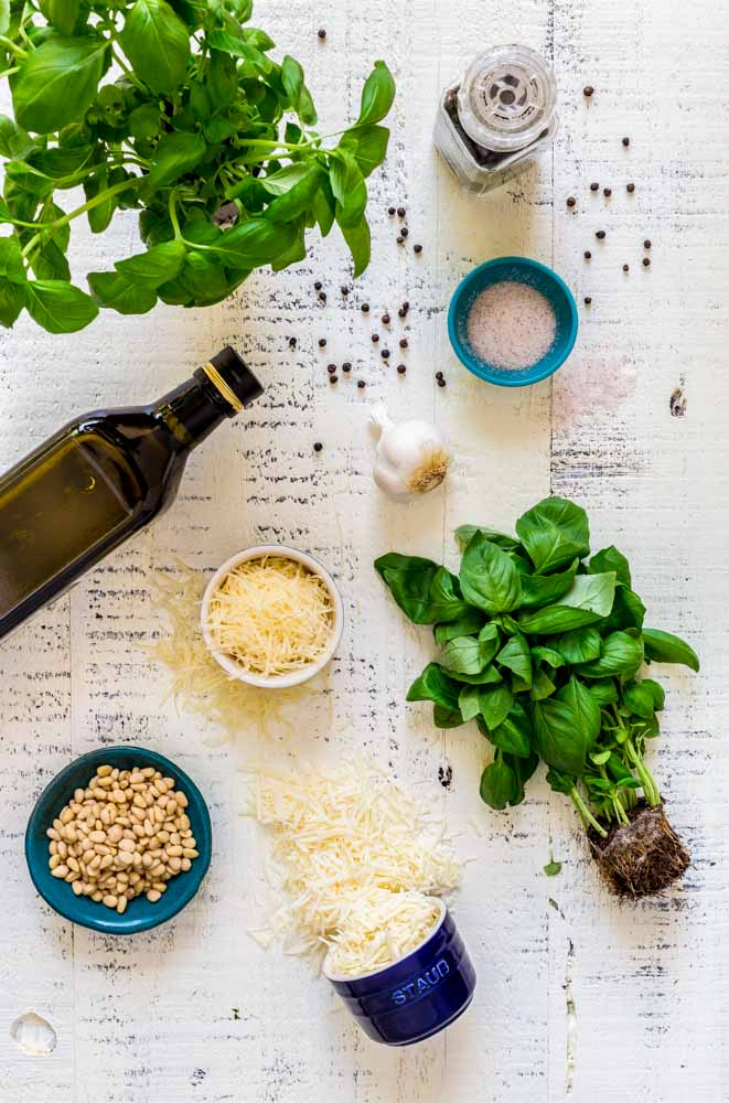 A flat-lay image of basil pesto ingredients artfully displayed on a white tabletop.