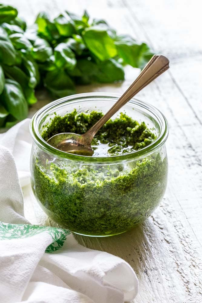 Homemade pesto sauce in a glass mason jar with a silver spoon on a white table.