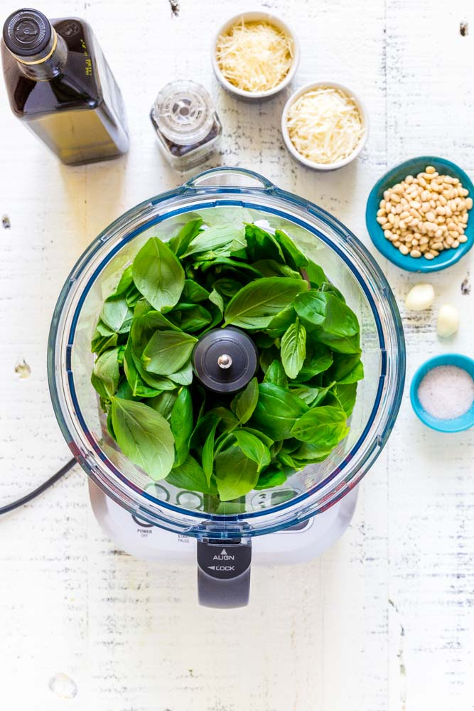 A top-down look at fresh basil leaves in the bowl of a Breville food processor.