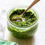 Homemade basil pesto in a round Weck mason jar with a silver spoon.