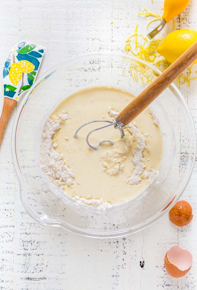 A Dutch dough whisk in a glass mixing bowl with wet and dry ingredients for scones.