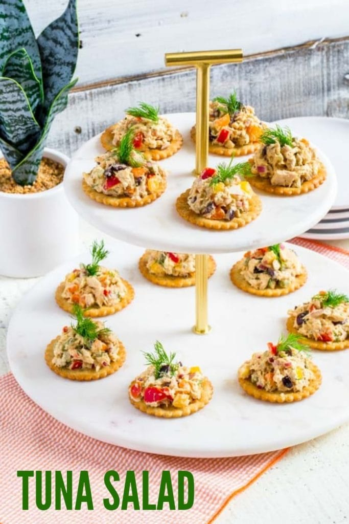 Tuna Salad on round crackers with a feathery sprig of dill served on a tiered tray.