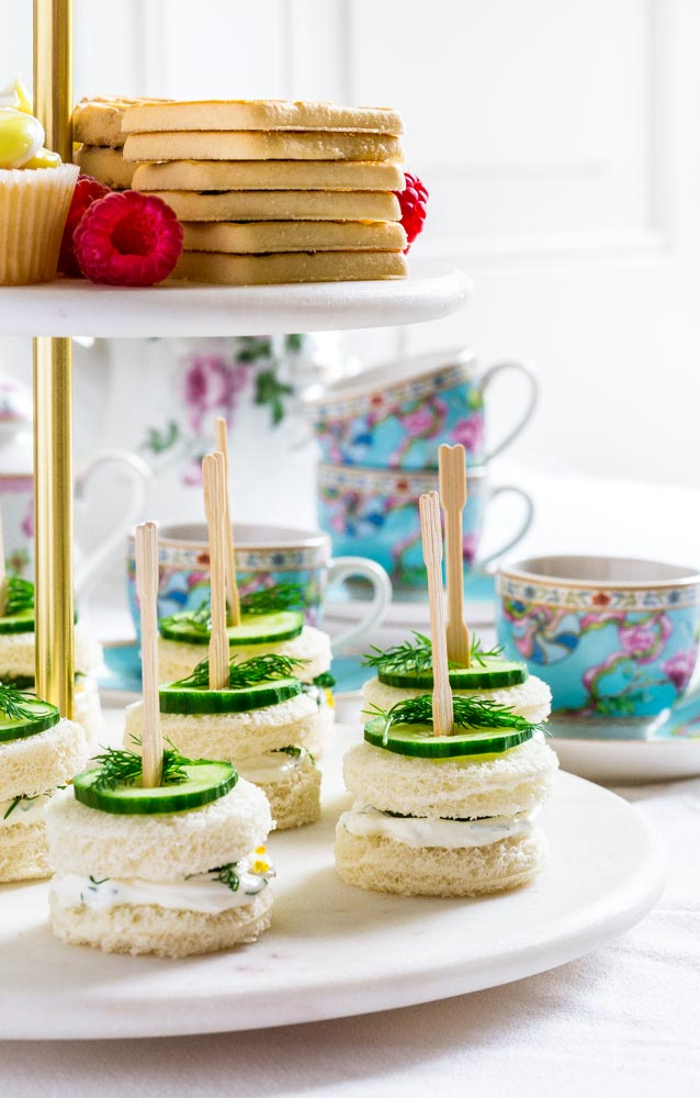 Cucumber and cream cheese sandwiches on the bottom level of a marble-and-gold tiered tray.