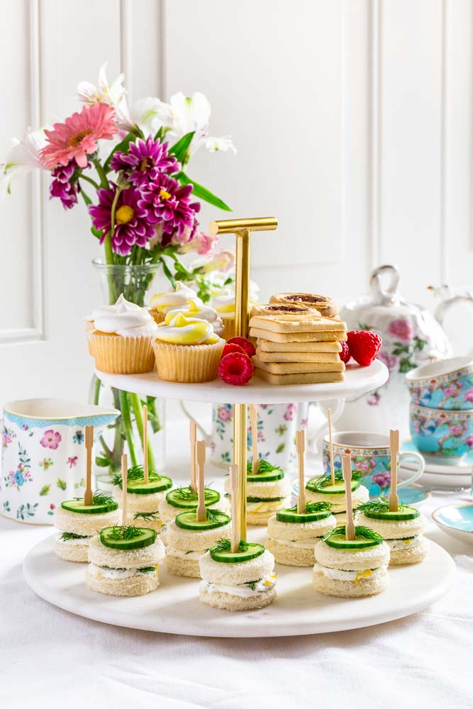 Tiered tray with cucumber tea sandwiches and bite-size desserts.