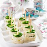 Cucumber tea sandwiches on a white serving tray surrounded by a tea pot and tea cups.