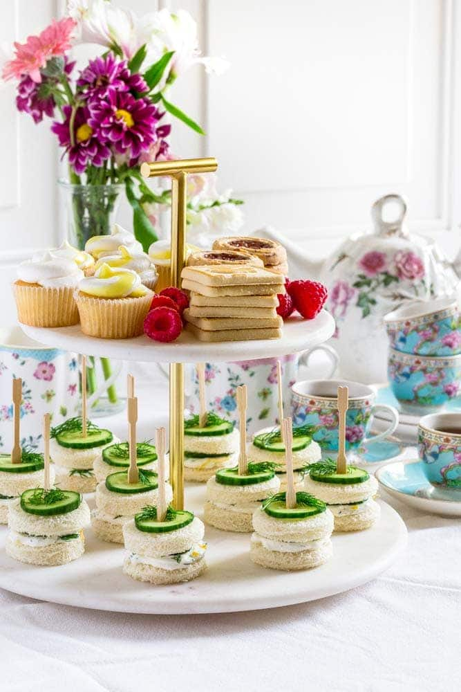 Cucumber sandwiches and small bite-size desserts on a 2-tiered marble and gold tray.