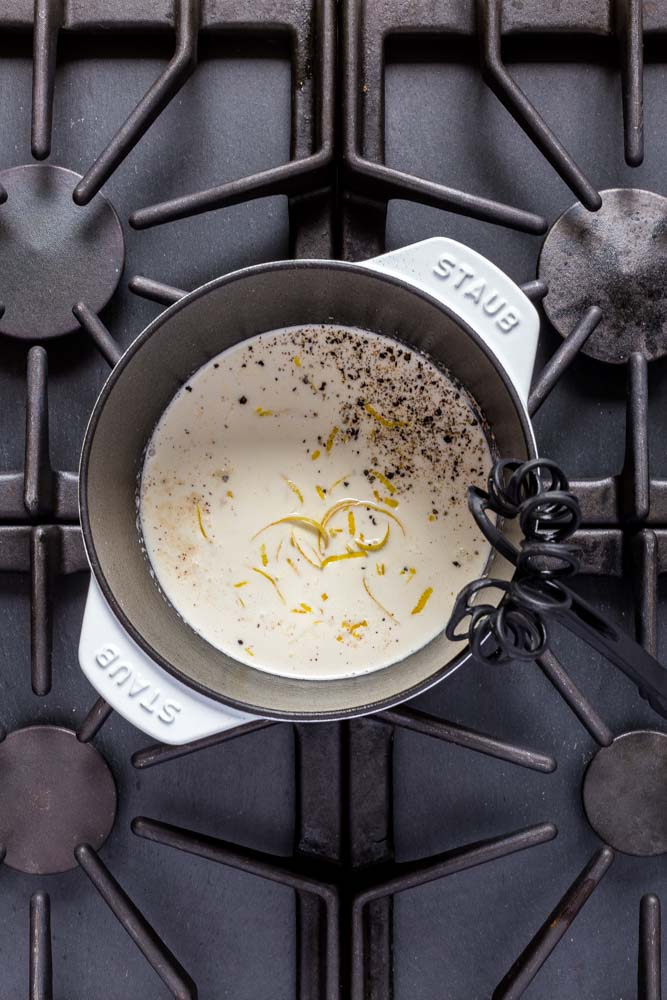 Creamy pasta sauce in a white Staub cocotte on a 6-burner stove.